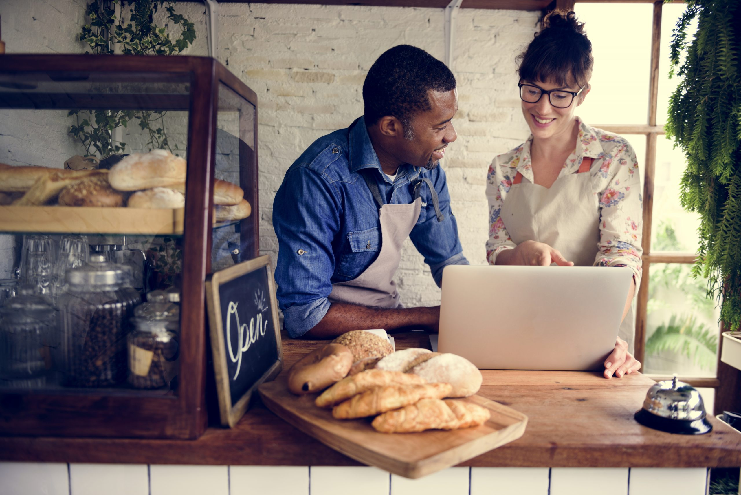 Buying a business. A happy business owner working in a bakery talking to a female customer.