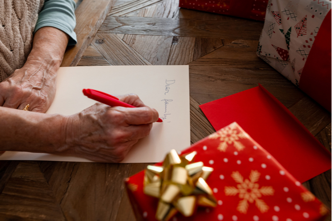 Brown Lawyers Share Your Stories article - Person writing letter to family with Christmas present in the foreground.