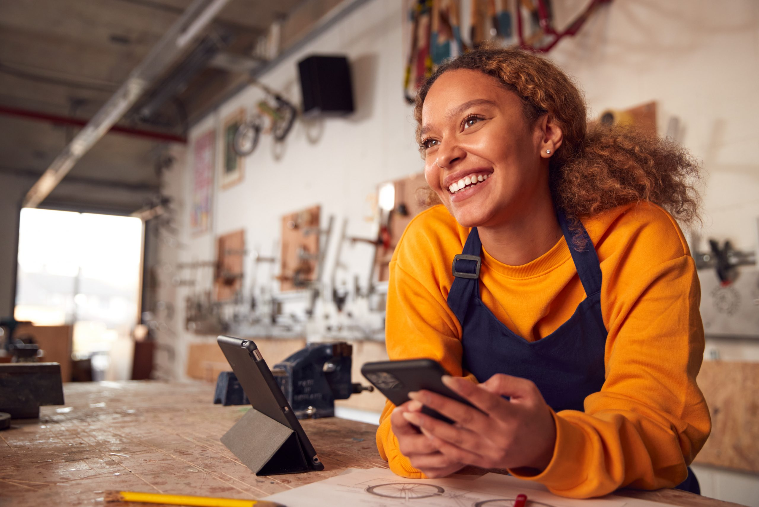 Woman-with-phone-smiling-looking-away-in-workshop