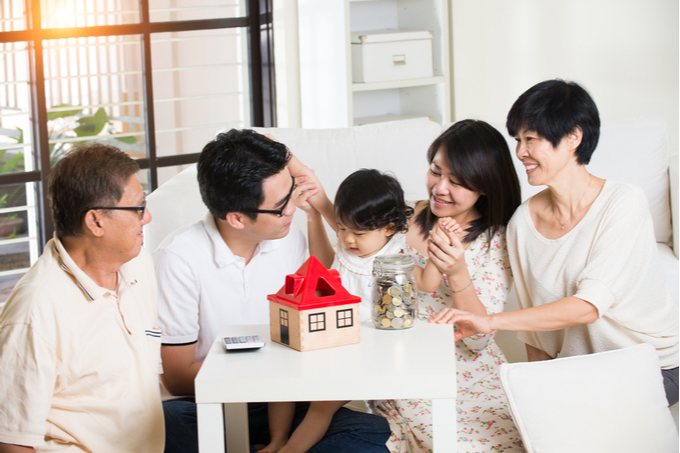 Smiling multigenerational family gathered around a table with a toy house and piggybank. Representing BOMAD (Bank of Mom & Dad) concept. Blog article by Brown Lawyers.